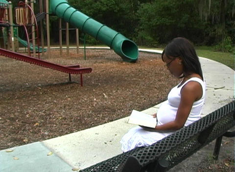 Beautiful Pregnant Woman Reading a Book Outdoors ( Stock Video Footage