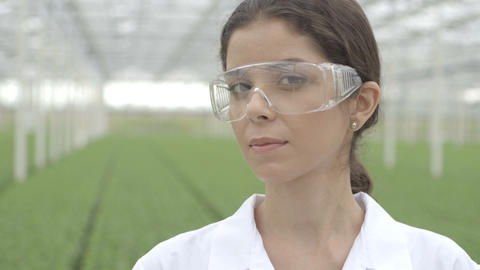 Scientist wearing safety glasses in a greenhouse Footage