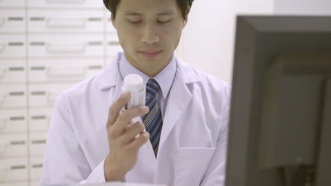 Pharmacist holding pill bottle while working in pharmacy Footage