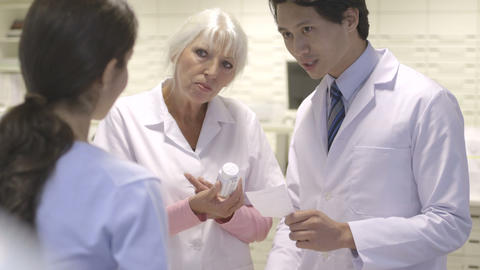 Male and female pharmacist giving medicine to patient Footage