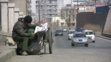 Poor worker reading newspaper along the road in Ch Footage