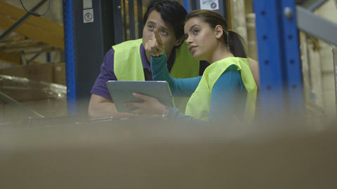Engineers using digital tablet and discussing in warehouse Footage