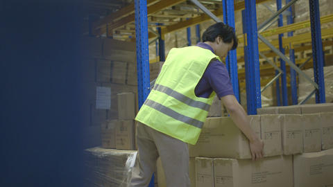 Warehouse worker carrying cardboard boxes Footage