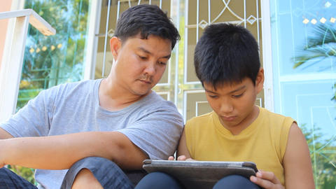 Father and son using tablet PC together Footage
