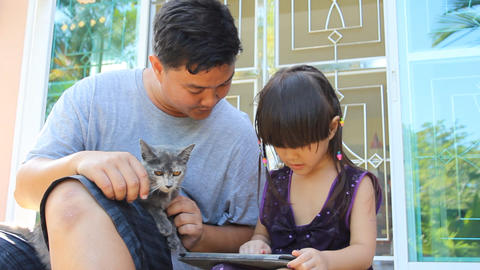 Father,daughter and cat play digital tablet Footage