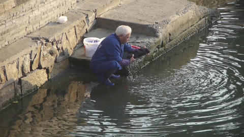chinese man wash cloths in river Animation