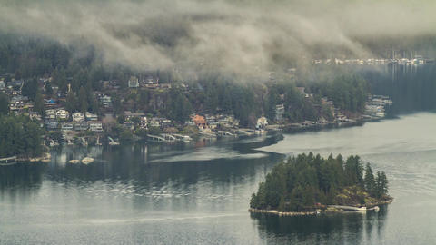 Clouds and fog by an island and houses Footage