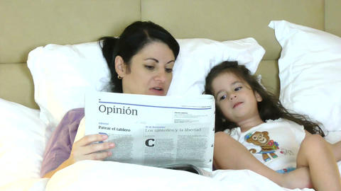 mother and child reading newspaper in bed having f Footage