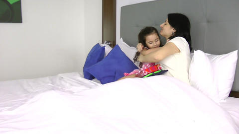 Little girl giving a gift to her mother in the bed Footage