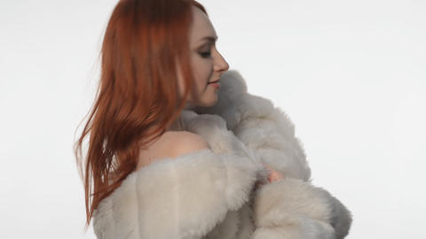 Red-haired Girl Posing In A White Fur Coat stock footage