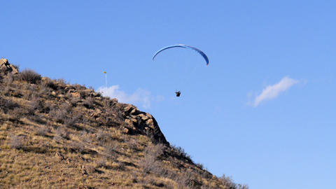 Paraglider hovers over Land Footage