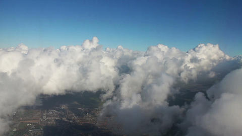 Airplane flying over city and clouds, shot from th Footage