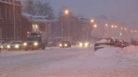 cars on a city street in a blizzard at dawn Footage