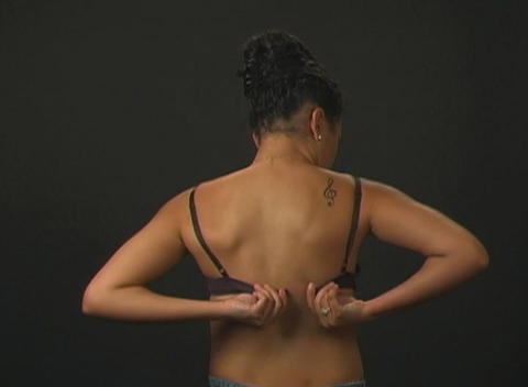 Beautiful Young Woman Putting on Her Bra (1) Stock Video Footage