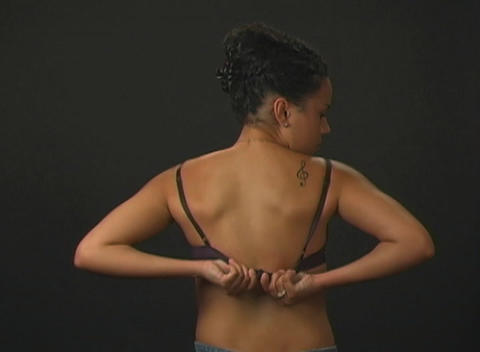 Beautiful Young Woman Putting On Her Bra (1) stock footage