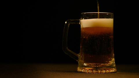 Pour the beer into a glass on a black background Footage