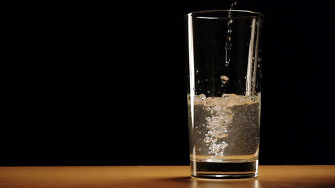 Water is slowly poured into a glass Footage