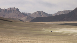 Jeep drives through empty beautiful landscape Pami Footage