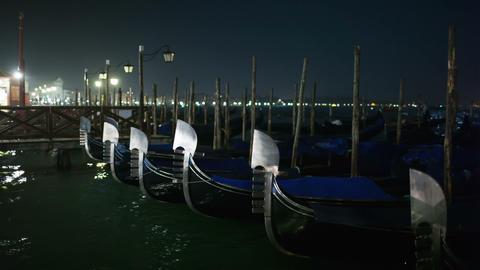 Venetian gondolas tied near the pier at night on S Footage