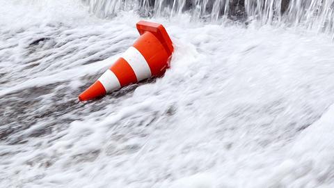 Orange traffic cone under a waterfall Footage
