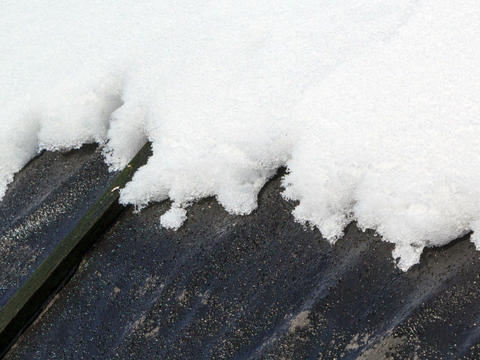 On a black roof snow melts. Time Lapse. 640x480 Footage