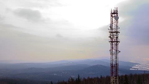 Mobile communication tower over the winter forest. Footage