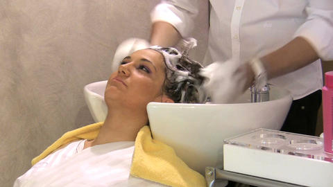 Happy girl washing hair in Hairdresser salon Footage