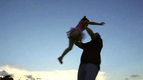 father rotate little girl with sunset background Footage