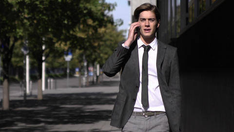 Happy Businessman Coming Outside From Office Building While Talking on Cellphone Footage
