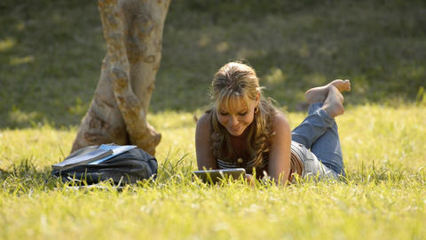 woman lying on grass with books and tablet pc studying Footage