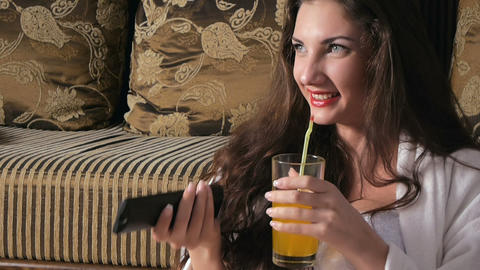 Girl drinking juice and watching television smilin Footage