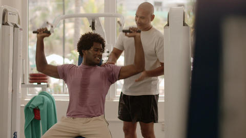 fitness trainer helping man in gym Footage