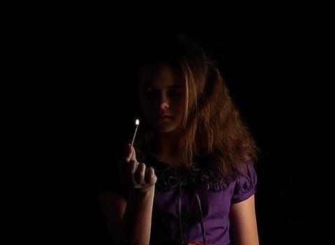 Beautiful Adolescent Girl Lights a Match (1) Stock Video Footage