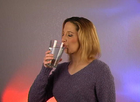 Beautiful Young Blonde Drinks a Glass of Water Footage