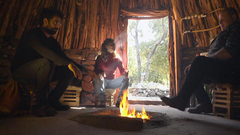 Tourists Sitting Around Fireplace In Hut, Sardinia Stock Video Footage