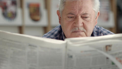 Elderly man reading newspaper in library Stock Video Footage