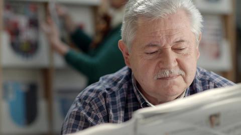 Elderly man reading newspaper in library Footage