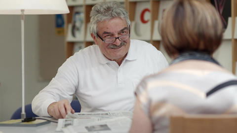 Old man reading newspaper with wife in library Footage