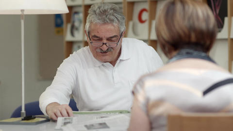 Old man reading newspaper with wife in library Stock Video Footage