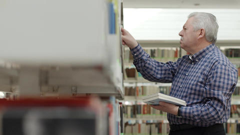Senior man choosing book from shelf in library Stock Video Footage