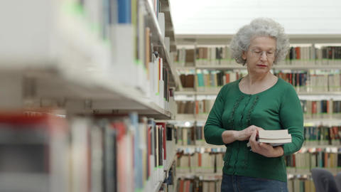 Senior woman reading book in library Stock Video Footage