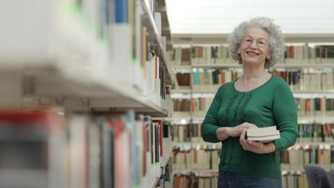 Senior woman reading book in library Footage