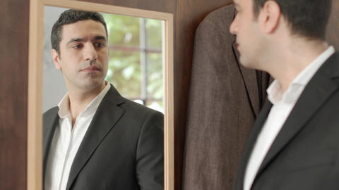Businessman trying suit and looking at mirror Stock Video Footage