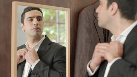 Businessman trying suit and looking at mirror Footage