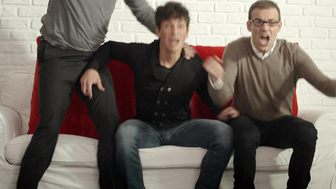 Three Male Friends Watching Sports Match On TV At  stock footage