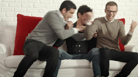 Three male friends watching sports match on TV at home Footage