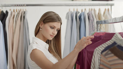 Woman choosing shirt in clothes shop Footage