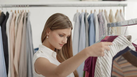 Woman choosing shirt in clothes shop Stock Video Footage
