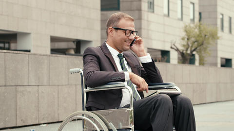 Businessman on wheelchair using tablet and talking Footage