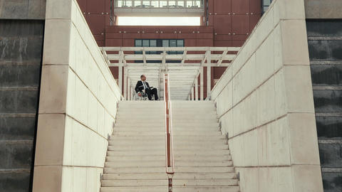 Businessman on wheelchair moving back from stairs Stock Video Footage